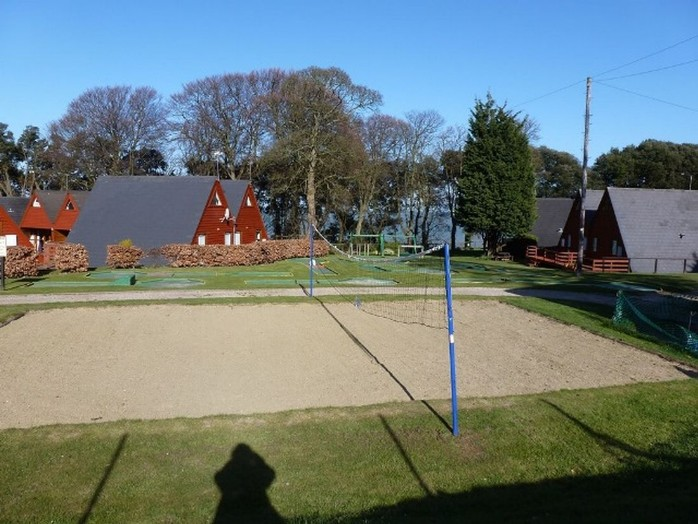 View of volleyball court with chalets behind